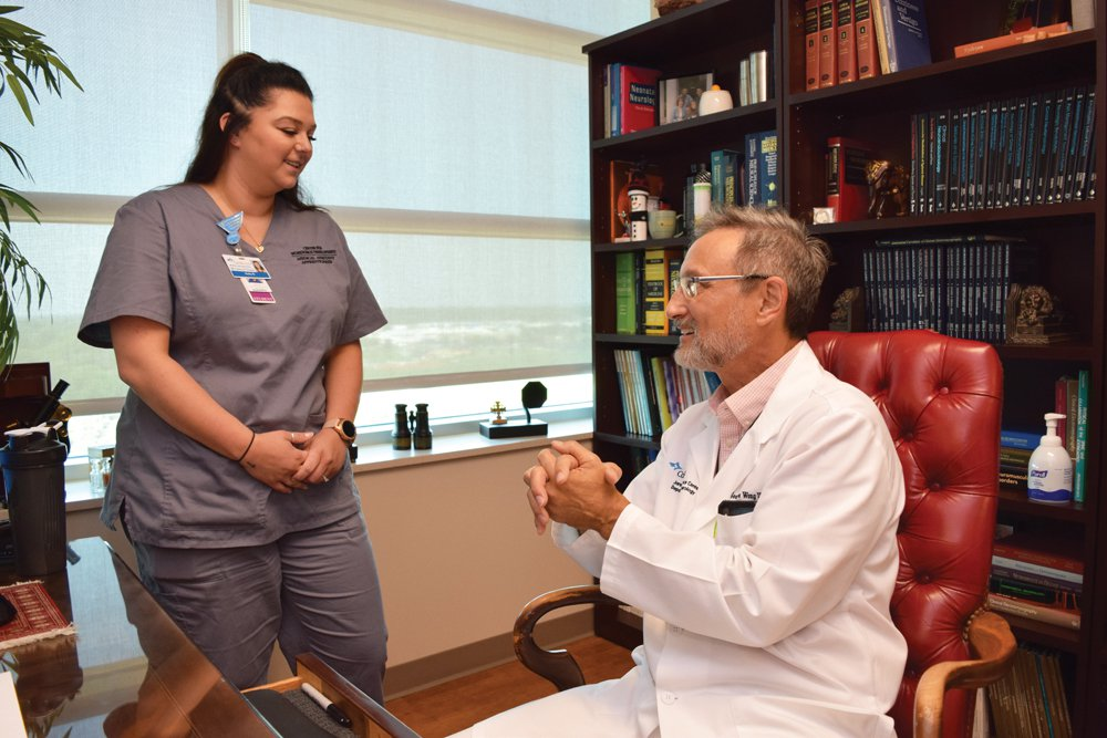 A medical assistant apprentice speaks with a physician.
