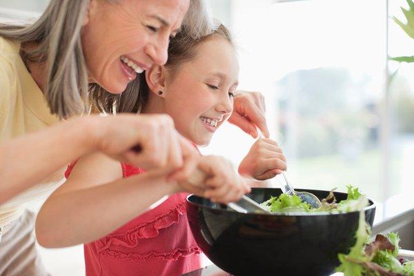 Grandma helping granddaughter make a salad