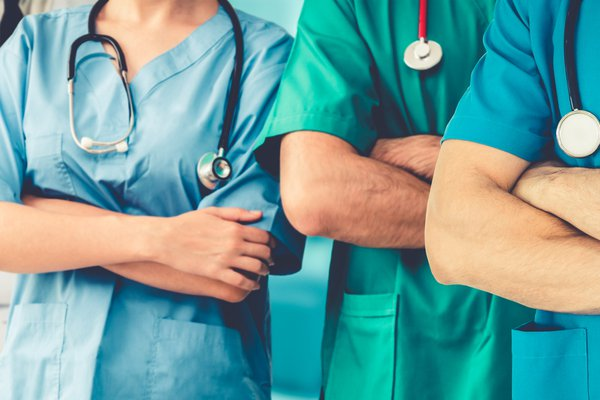 Medical professionals stand with their arms crossed.