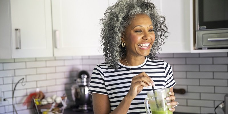 A middle-aged woman holding a healthy green drink stands in her kitchen and smiles.