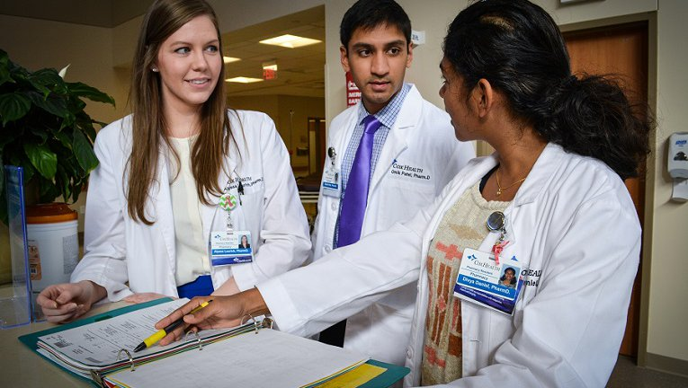Three pharmacy residents stand together and look at a patient file.