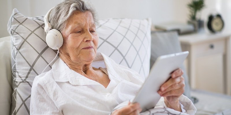 An elderly patient lying in a hospital bed wears headphones and holds a tablet while she listens to music.