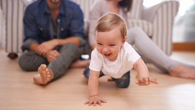 Couple watching their baby crawl.