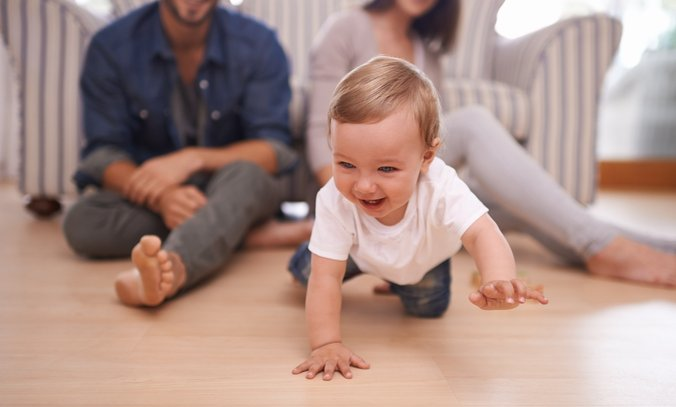 Young parents watch their child crawl on the floor.