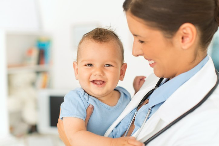 A provider holds a smiling baby.