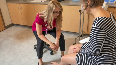 Laura examines a patient's legs.