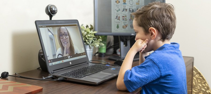 A young boy sits in front of a computer to attend his virtual speech therapy session.