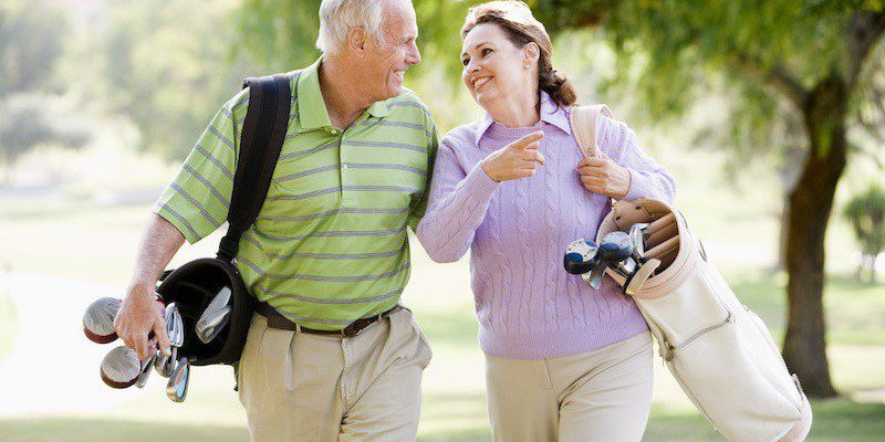 A man and a woman smile while walking on a golf course.
