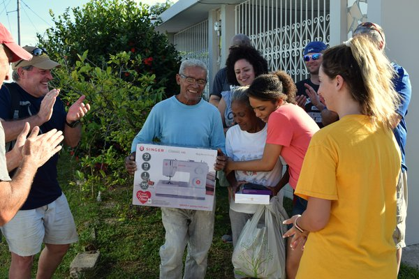 A group stands with Virginia after she receives her sewing machine.