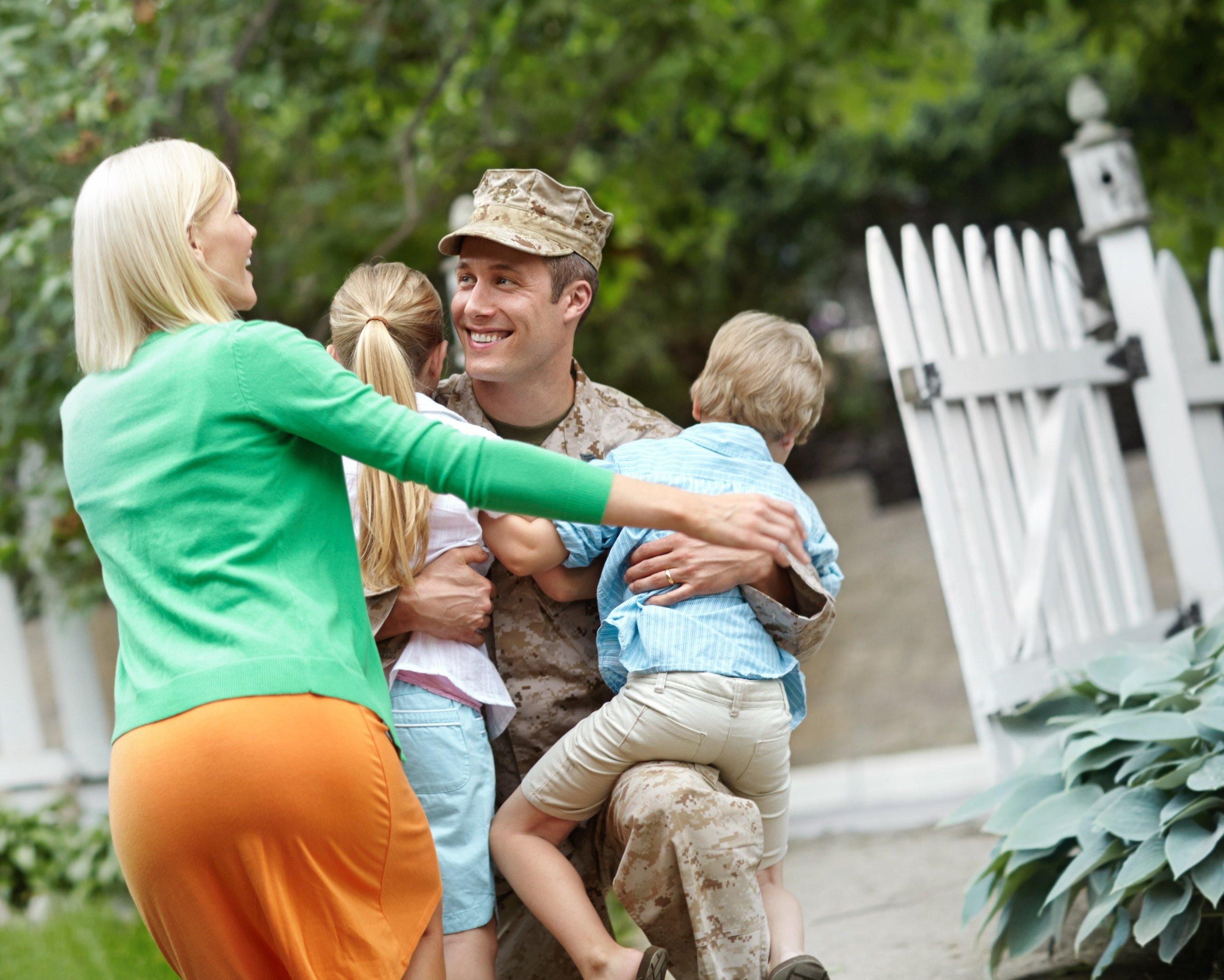 A family embraces a serviceman.