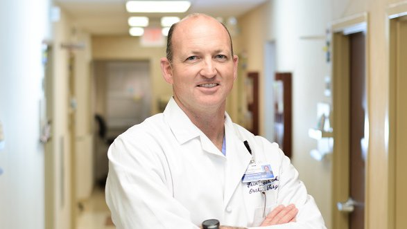 A male physician stands in a hospital hallway with his arms crossed.