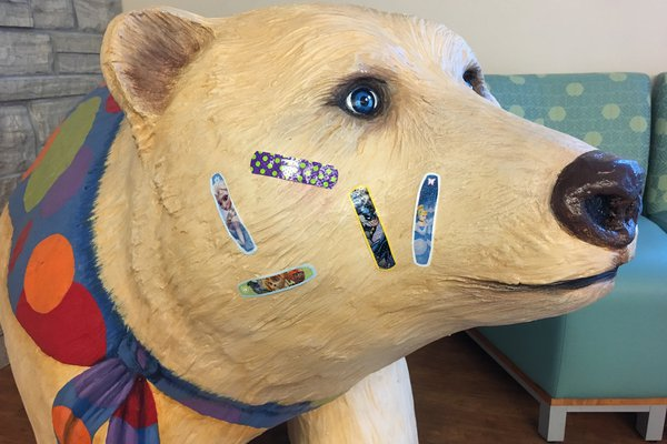 Bear statue with bandaids on it.