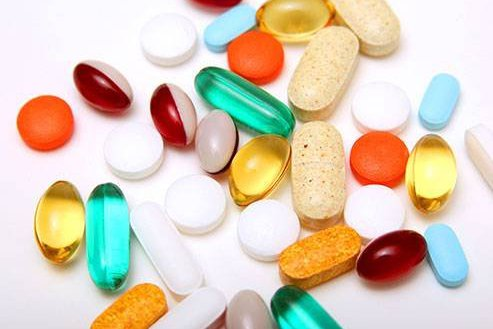 A variety of pills are shown on a table.