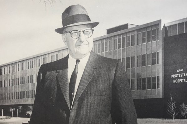 Lester E. Cox stands in front of Burge-Protestant Hospital.