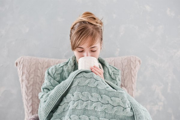 A woman sits under a blanket and consumes a warm drink.