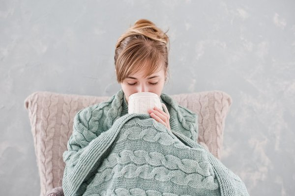 A woman sits under a blanket.