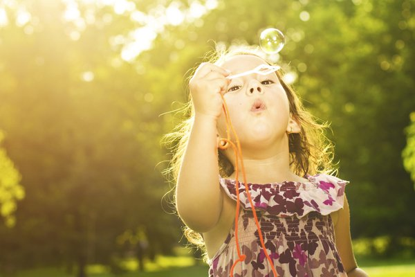 A little girl blows bubbles.