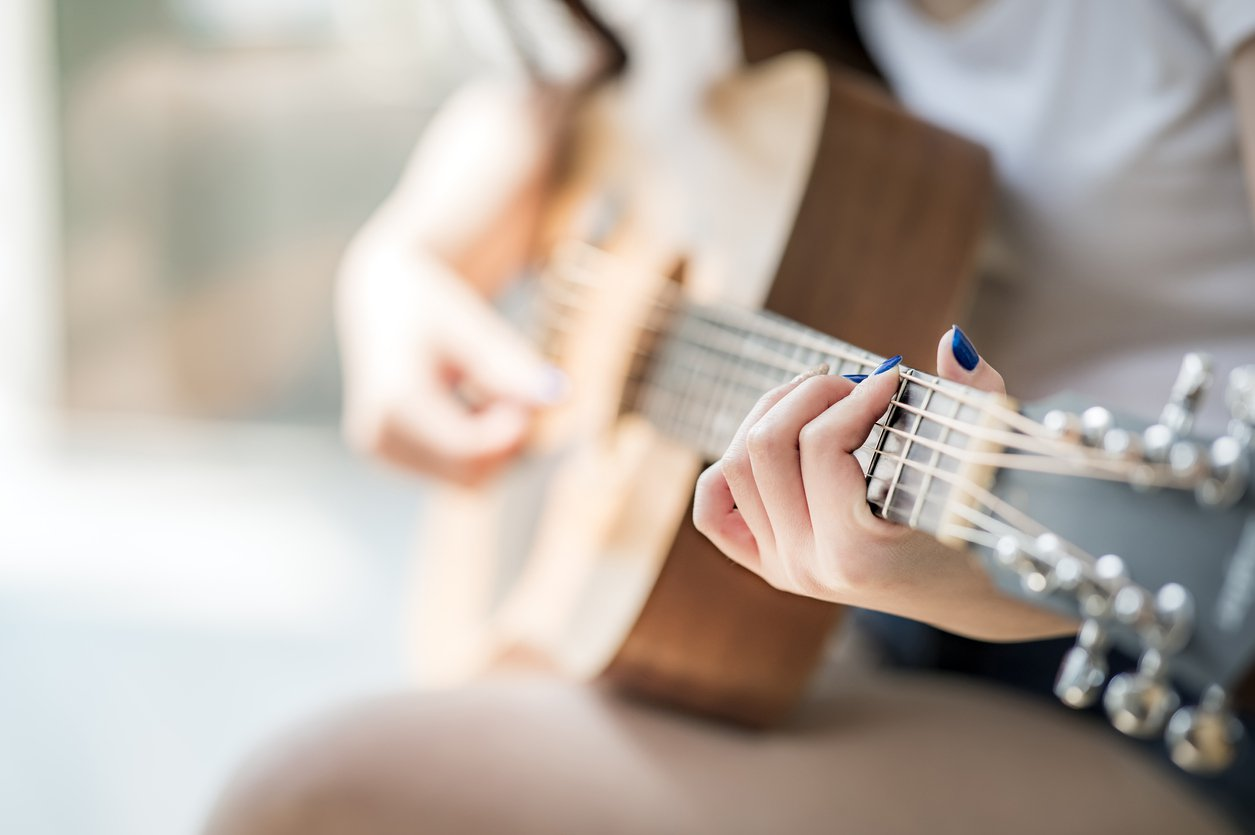 A woman plays the guitar.