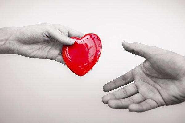 Hands exchange a heart.