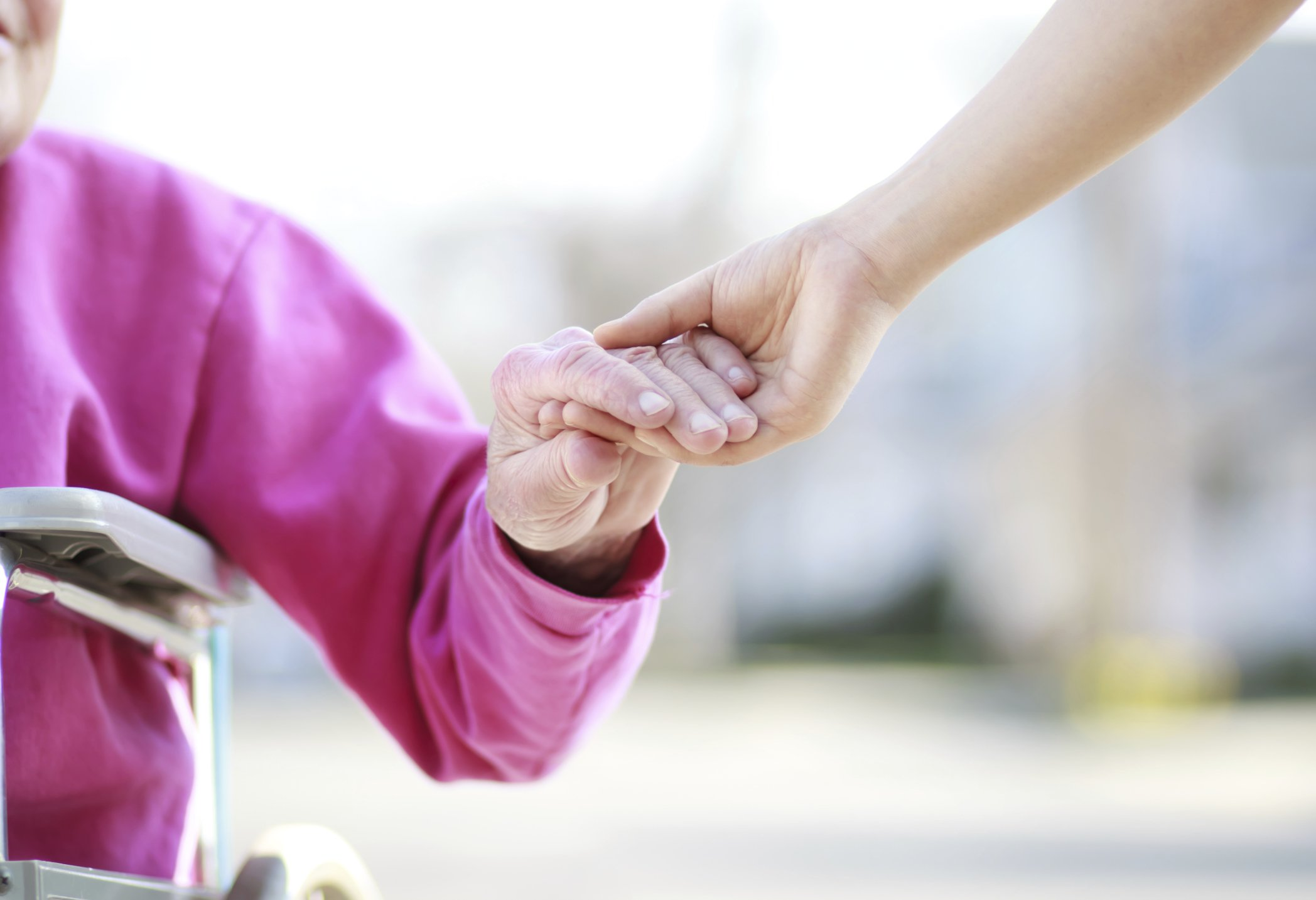 A caregiver holds hands with a patient.