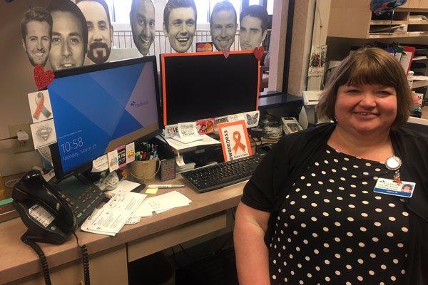 Joyce sitting in front of her desk.
