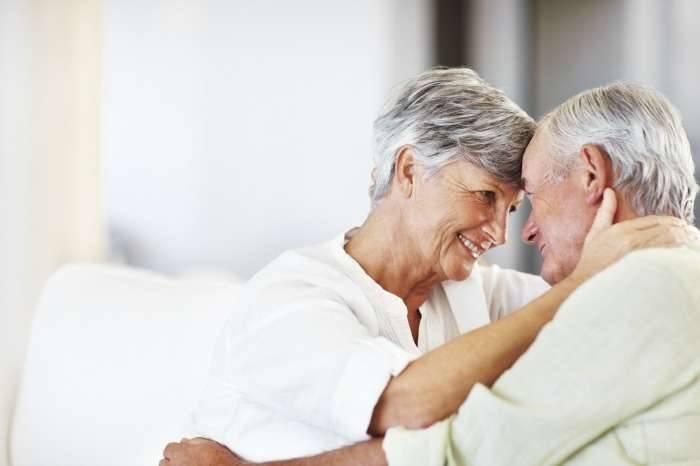 An older couple hugs each other.