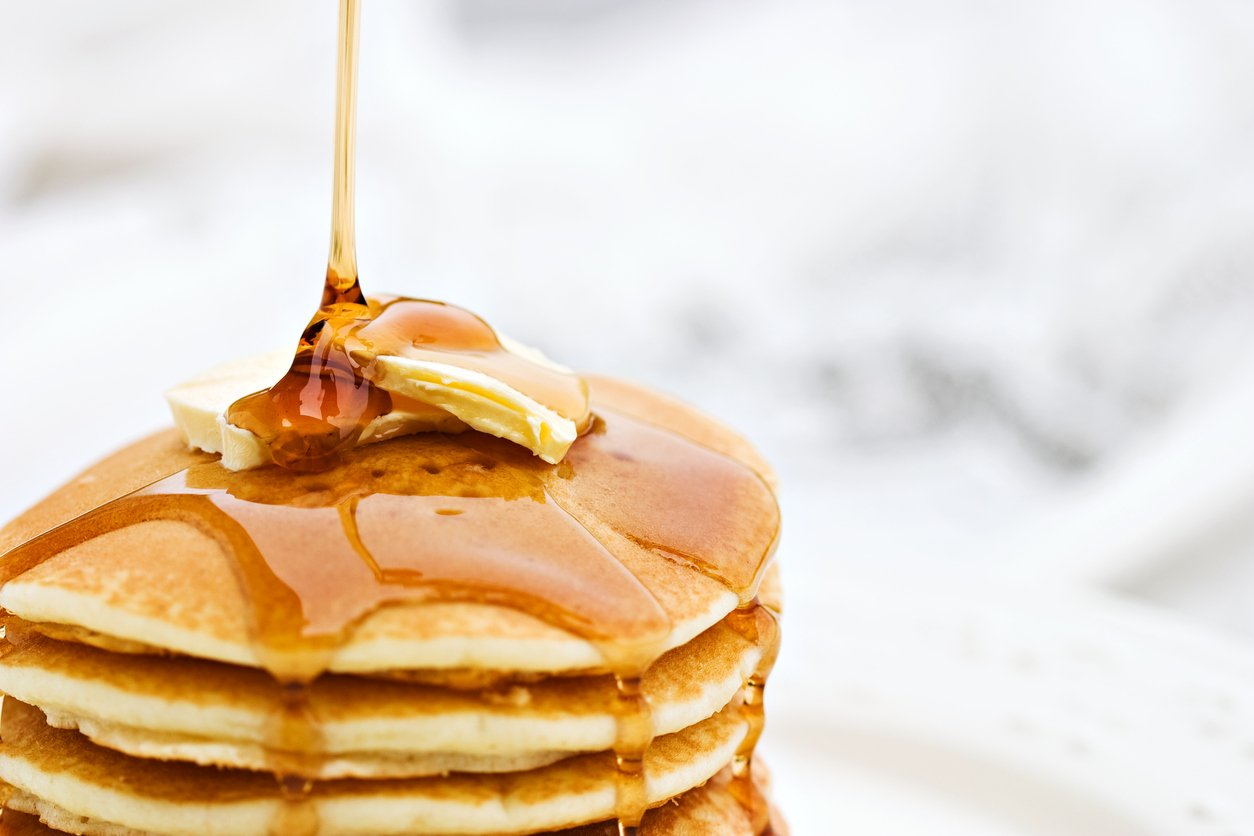 Someone pours syrup on a stack of pancakes.