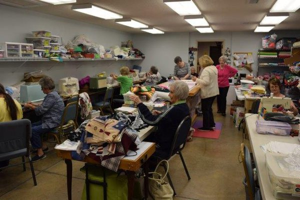 Volunteers sewing quilts.