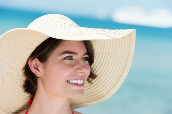 Woman on the beach wearing a floppy hat.