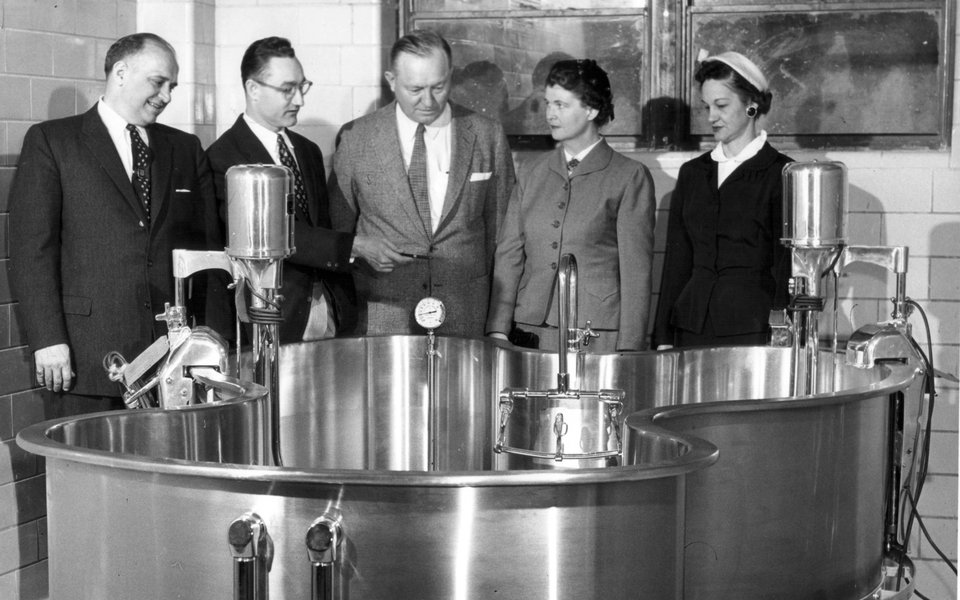A historic photo of CoxHealth executives standing around a water therapy tank