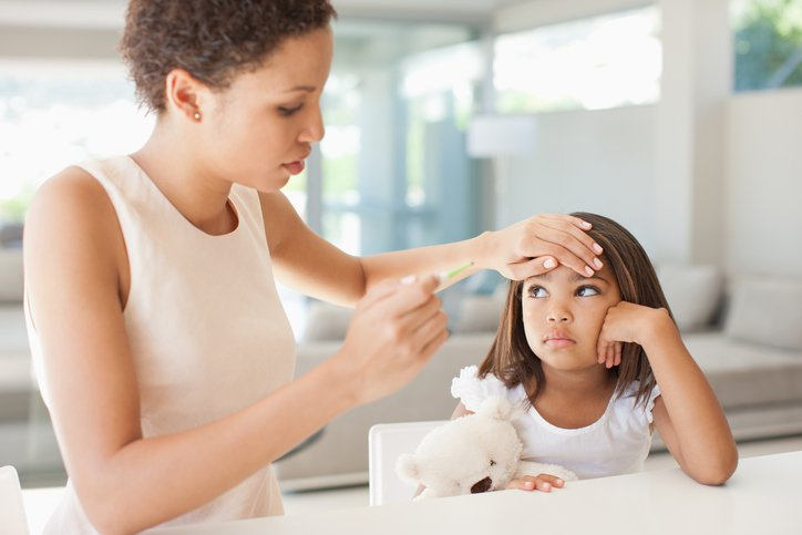 A woman feels a child's forehead for fever.